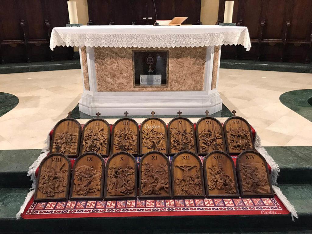 Las 14 estaciones del Viacrucis talladas en madera sobre las escaleras delante del altar de una iglesia.